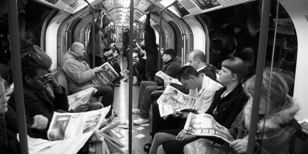 people reading newspapers on subway
